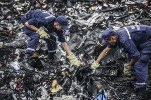 Dos agents busquen entre les restes del vol MH17 de Malaysia Airlines, el 20 de juliol a Donetsk (Ucraïna).