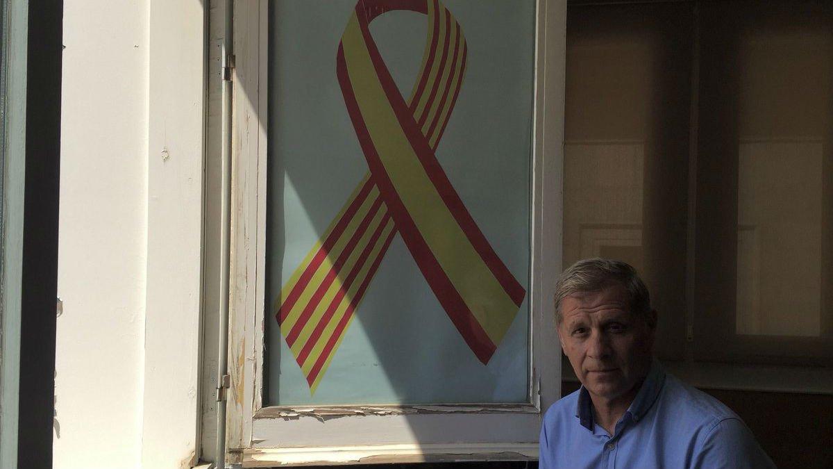 Alberto Fernández Díaz posa junto al lazo con las banderas de España y Catalunya colocado en la fachada del Ayuntamiento de BCN