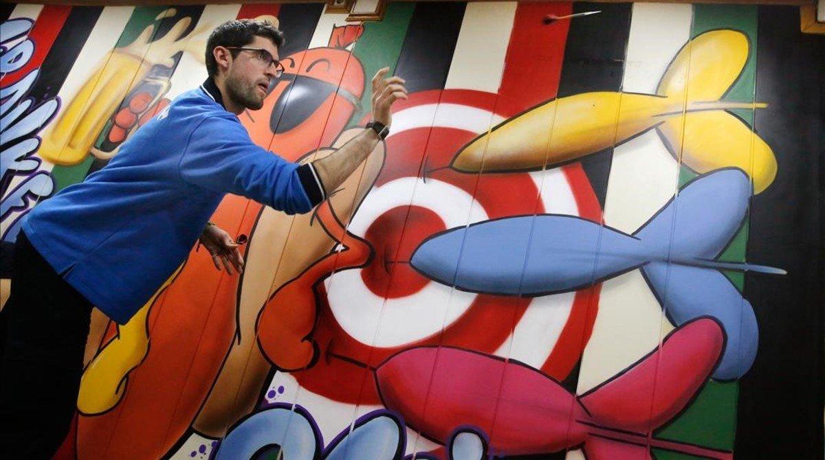 Un dardero lanza a la diana durante una partida de liga en un bar de Santa Coloma.