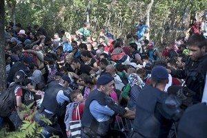 Immigrants i refugiats trenquen el cordó policial a Tovarnik, ahir.