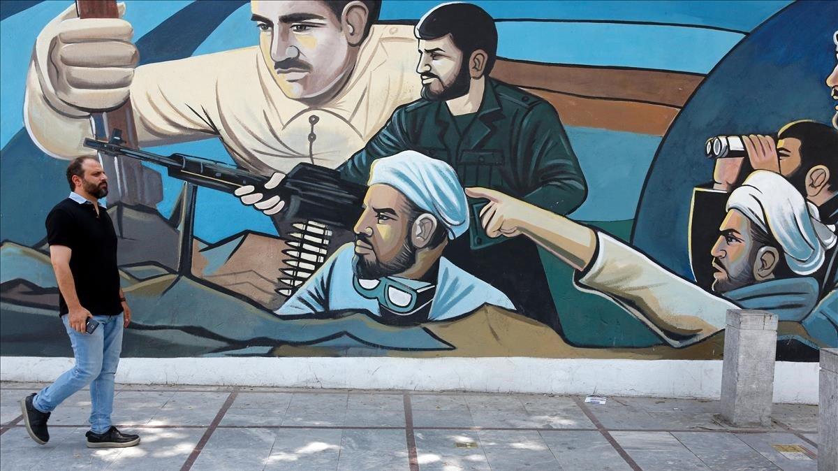Un hombre camina delante de un muralen Teherán (Irán) sobre el acuerdo nuclear.