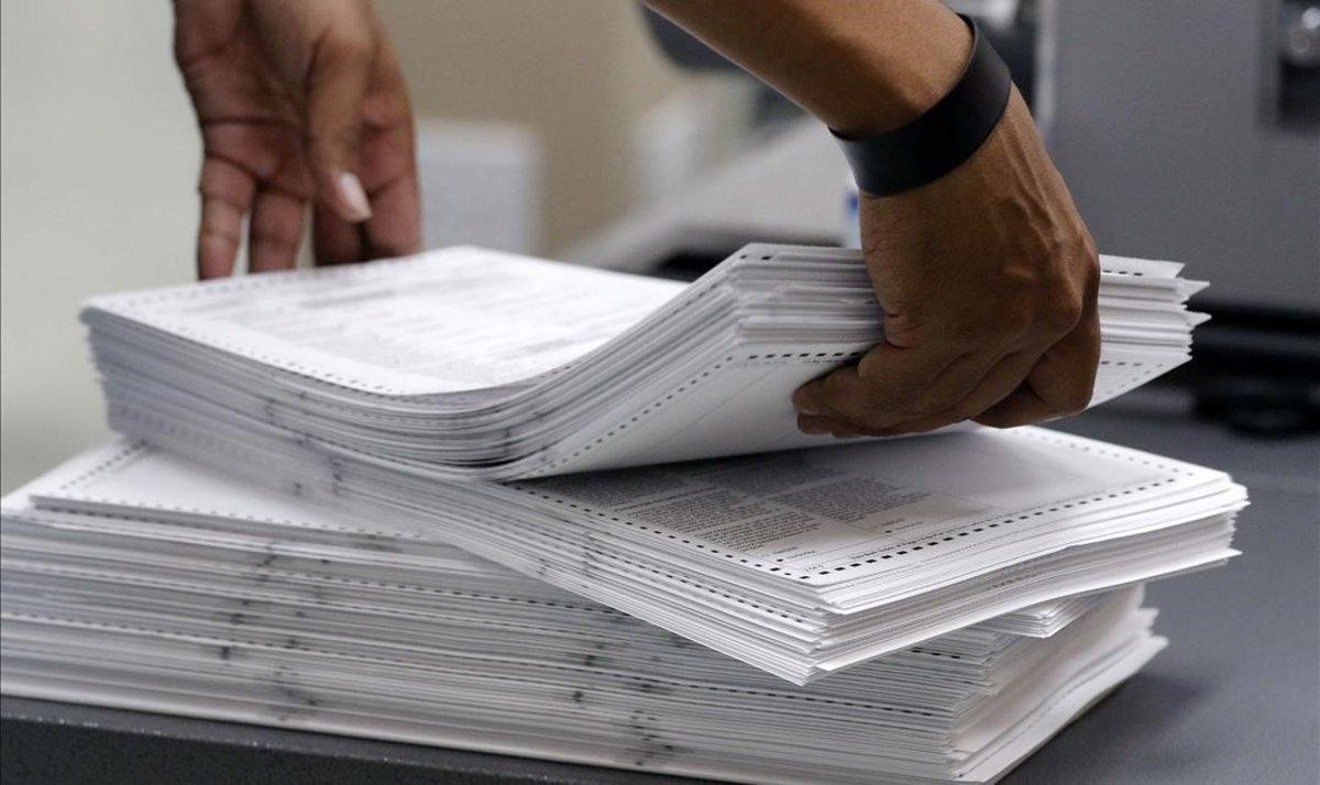 Un miembro del personal electoral carga sufragios en la Oficina del Supervisor Electoral del Condado de Broward, en Florida.