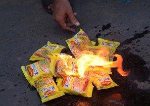 Activistas sociales de la India queman paquetes de fideos Maggi durante una protesta en Kolkata.