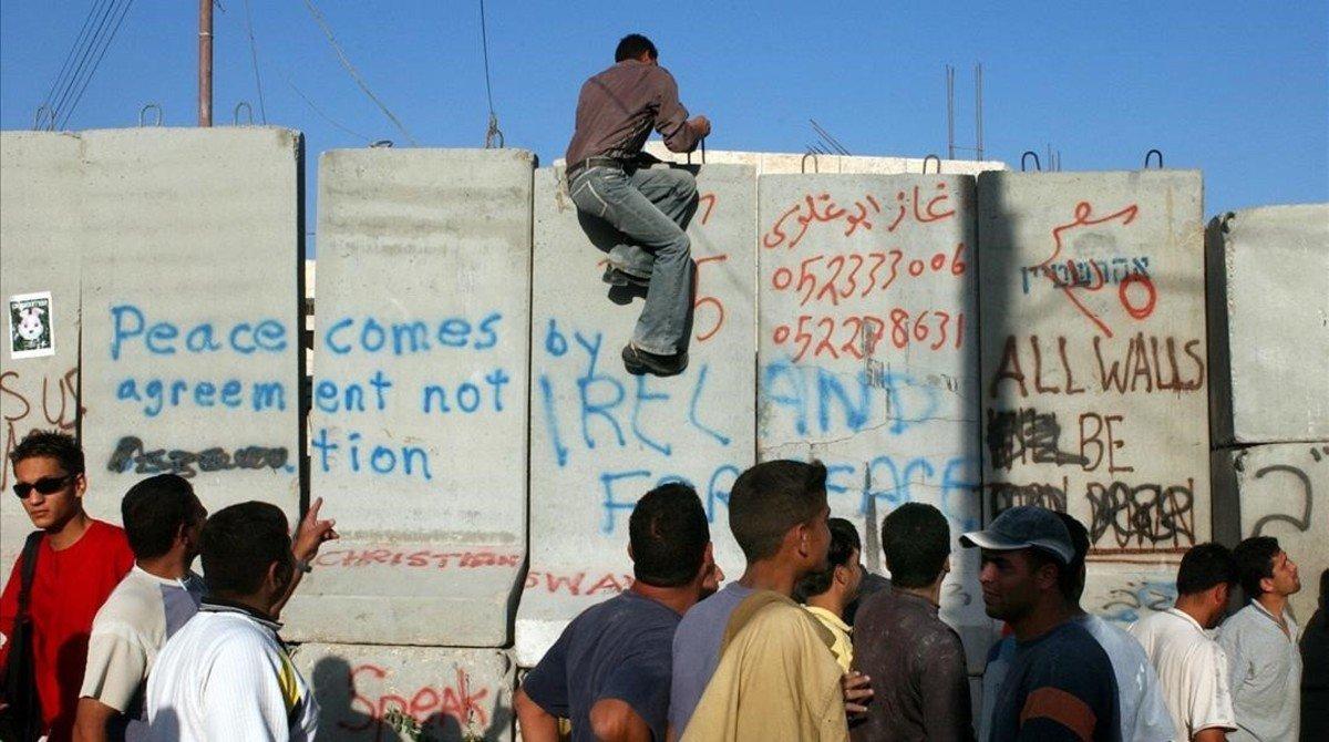 Un palestino trepa por un bloque de cemento mientras otros caminan junto a la barrera israelí que separa la población cisjordana de Abu Dis, en las afueras de Jerusalén, el 19 de julio del 2004.