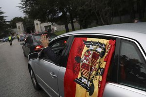 A passenger waves from a car displaying a pre-constitutional Spanish flag as it enters the Valle de los Caidos (The Valley of the Fallen), the mausoleum holding the remains of Spanish dictator Francisco Franco, in San Lorenzo de El Escorial, outside Madrid, Spain, November 20, 2018. REUTERS/Susana Vera