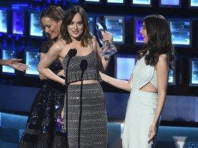 Dakota Johnson, a la izquierda, recoge el premio como mejor actriz dramática por 'Cincuenta sombras de Grey' mientras se aguanta el vestido roto por detrás.