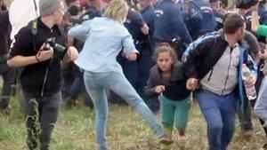 Imagen de un video en la que se ve a la reportera Petra László como hace la zancadilla a una niña refugiada que huye de la policía en el campo deRoszke.