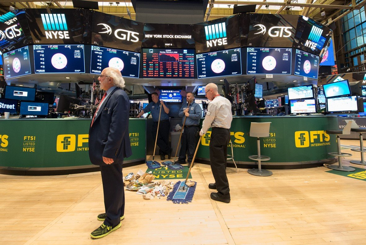 TOPSHOT - Personal sweep the floor after the closing bell of the Dow Industrial Average at the New York Stock Exchange on February 5, 2018 in New York.