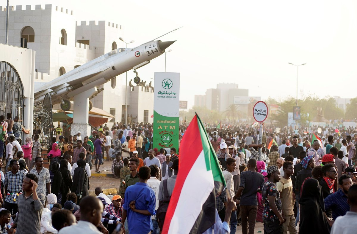 Sudanese demonstrators hold national flags and chant slogans as they protest against the army s announcement that President Omar al-Bashir would be replaced by a military-led transitional council outside Defence Ministry in Khartoum Sudan April 11 2019 REUTERS Stringer