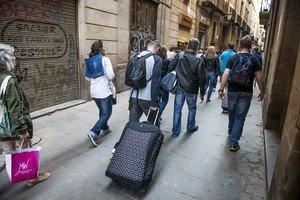 Turistas con maletas en el centro de Barcelona.