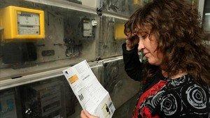Una mujer mira una factura real de Endesa.