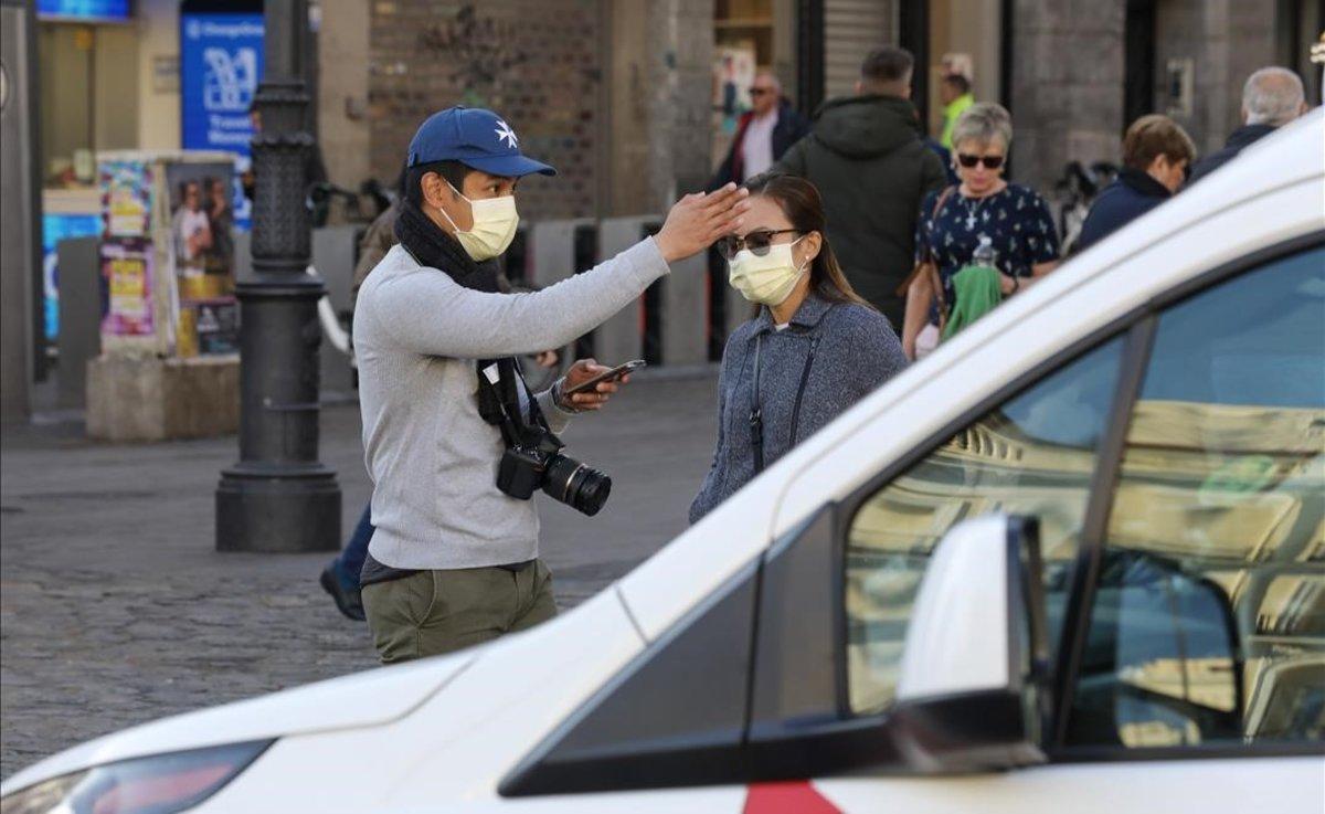 Una pareja pasea por Madrid protegida con mascarillas, por el riesgo de coronavirus.