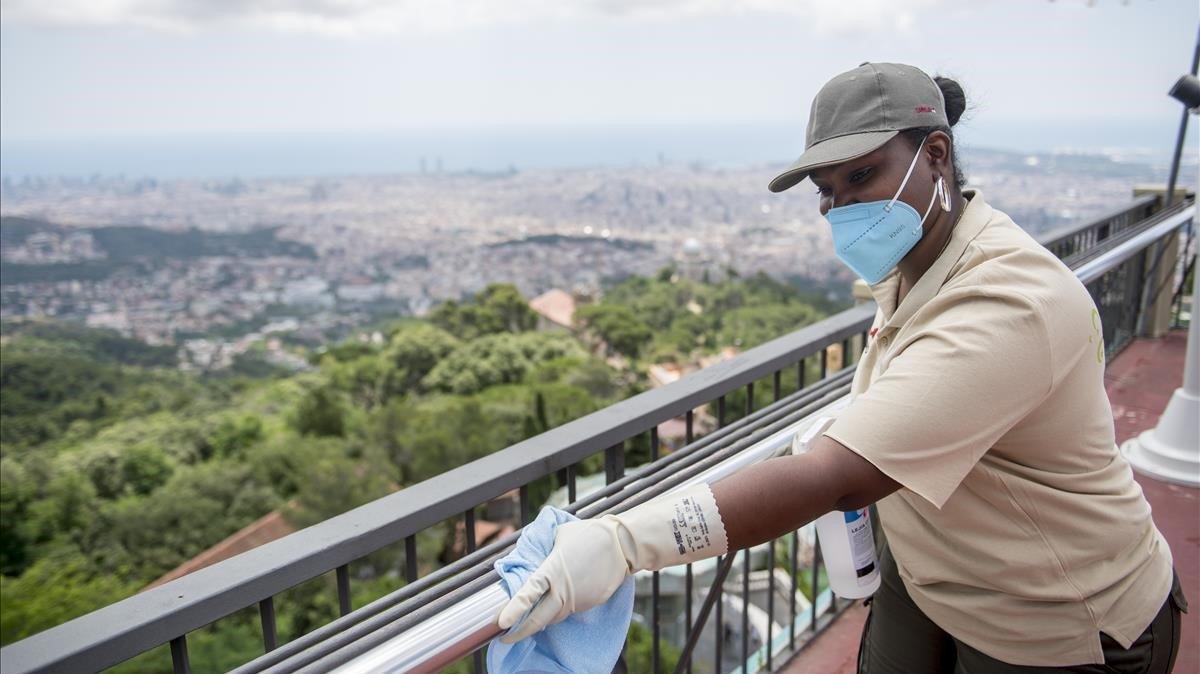 Una trabajadora desinfecta una barra sujetamanos del Tibidabo, el pasado 4 de julio.