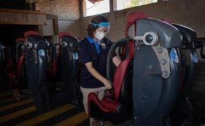 Una trabajadora de Port Aventura World prepara el asiento de una atracción.