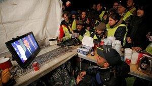 Unos chalecos amarillos siguen el discurso de Macron por televisión, en La Ciotat, cerca de Marsella.