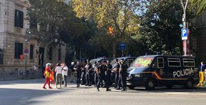 Varias personassaludan a unos agentes de la Policía Nacional, en Barcelona.