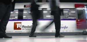 Varios pasajeros descienden de un tren de Rodalies en la estación barcelonesa de Sants.