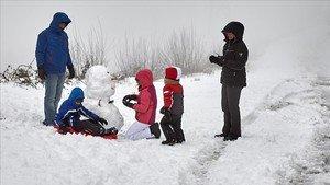 Una familia juega con la nieve en la localidad de O Cebreiro, en Lugo, este sábado.