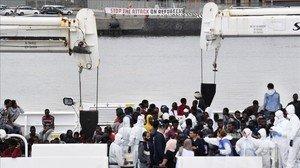 Unos activistas cuelgan una pancarta a favor de los refugiados durante el desembarco de inmigrantes llevado a cabo el 13 de junio en el puerto de Catania (Sicilia) por el barco de los Guardacostas italianos Diciotti.