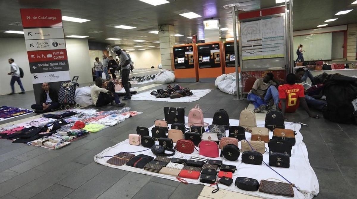 Vendedores de top manta, en el vestíbulo de la estación de Renfe de la plaza de Catalunya, la semana pasada. Al fondo, máquinas expendedoras de billetes.