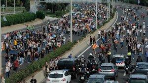 Autopista al aeropuerto de El Prat con gente caminando por la misma