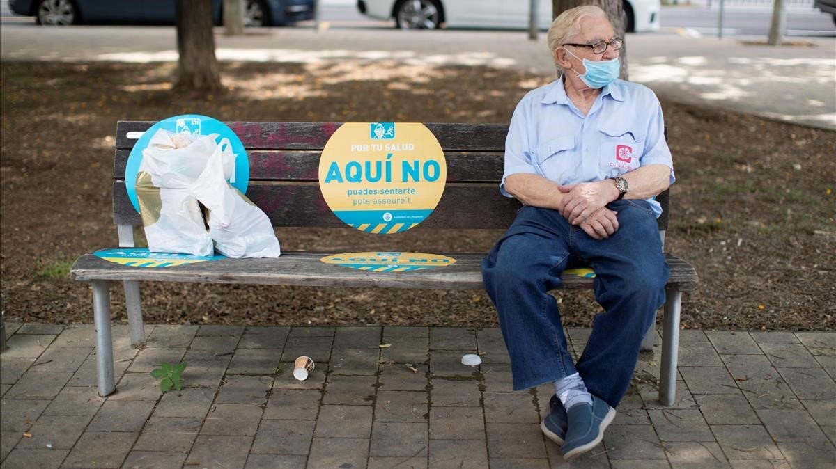 Un hombre descansa en un banco de Barcelona.