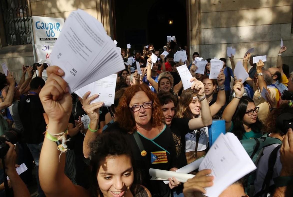 Varios estudiantes salen de la Universidad de Barcelona, con papeletas del referendum