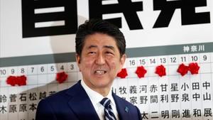 Abe sonríe mientras se dispone a colocar una rosa sobre el nombre de un candidato elegido para la Cámara baja, en la sede de su partido, en Tokio, el 22 de octubre.