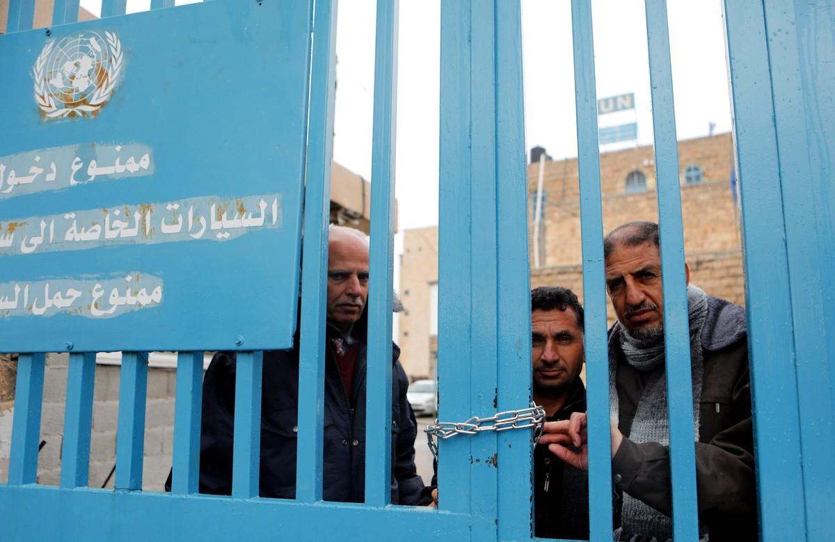 Un grupo de palestinos detrás de la valla de la oficina de la agencia de la ONU para los refugiados palestinos (UNRWA) durante una protesta en la ciudad de Cisjordania.