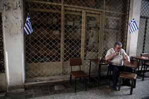 Un hombre bebé un café en Atenas.