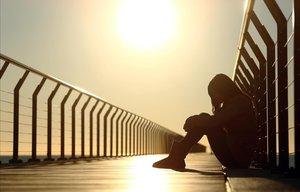 Adolescente triste sentada en el suelo.