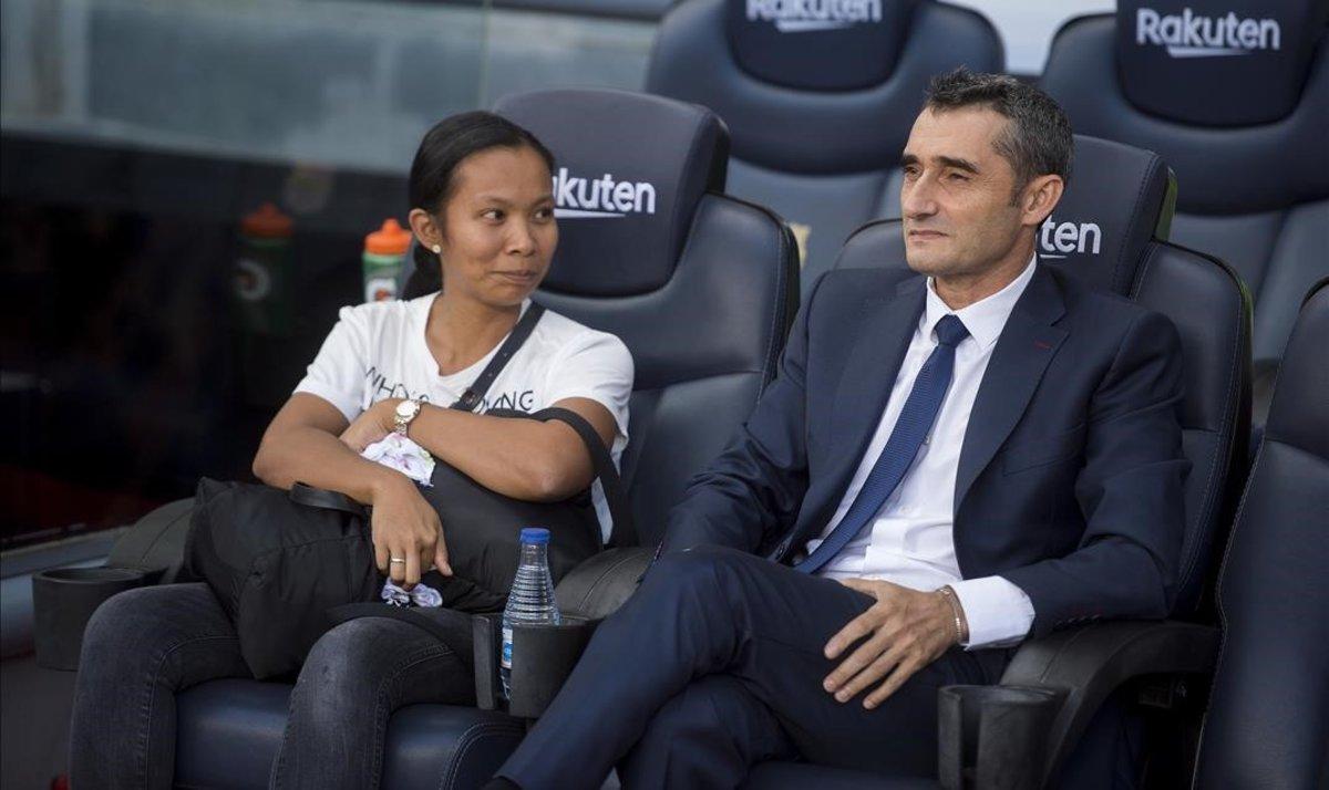 La asistenta de las hijas de Rakitic se sientaen el banquillo junto a Valverde antes del partido.