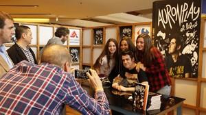 Un miembro de la corte de AuronPlay fotografía al youtuber con unas fans tras dedicarles el libro.