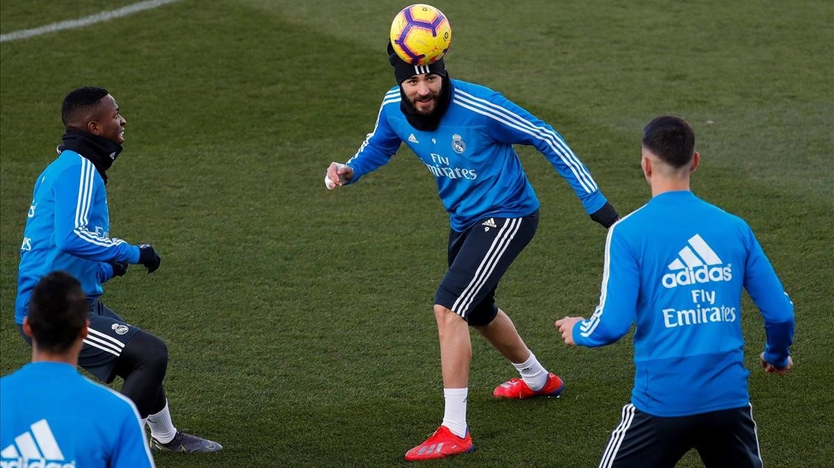 Benzema toca de cabeza ante Vinicius y Asensio en Valdebebas.