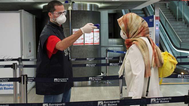 Caos en Italia para hacer los test a quienes regresan de otros países. En la foto, control de temperatura a una pasajera en el aeropuerto de Fiumicino, en Roma.