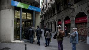 Varias personas haciendo cola frente a una oficina del Servei dOcupació de Catalunya (SOC).