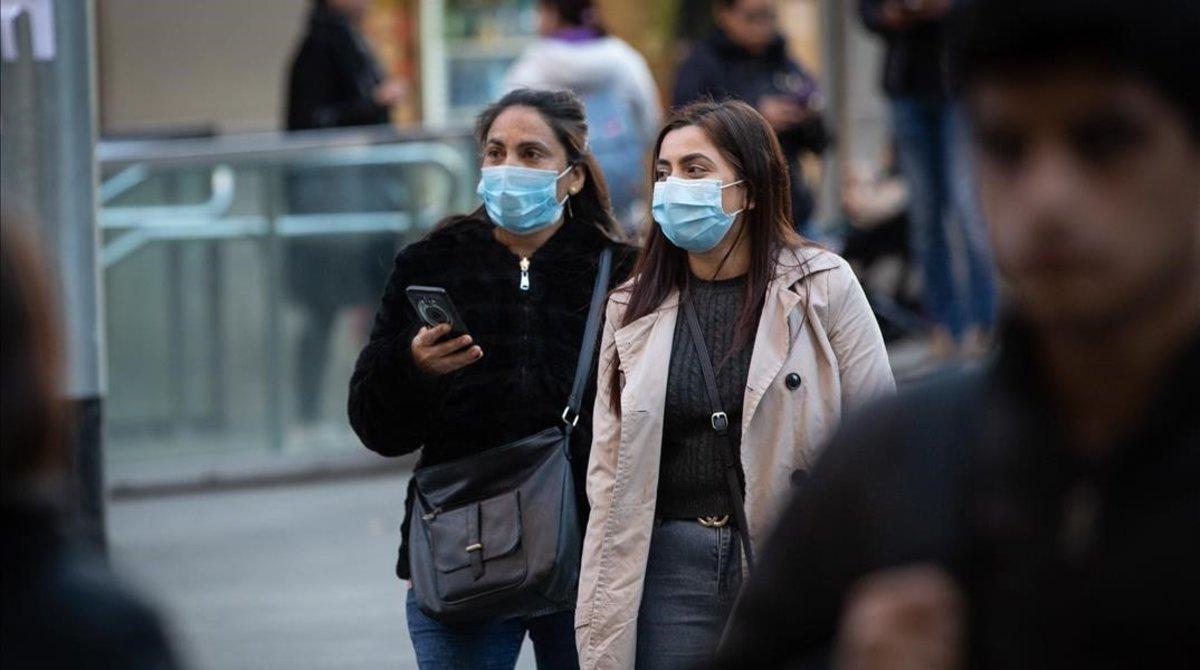 Dos mujeres con mascarilla por el centro de Barcelona, el 26 de julio.