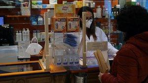 Una farmaceútica entrega una mascarilla a un usuario.