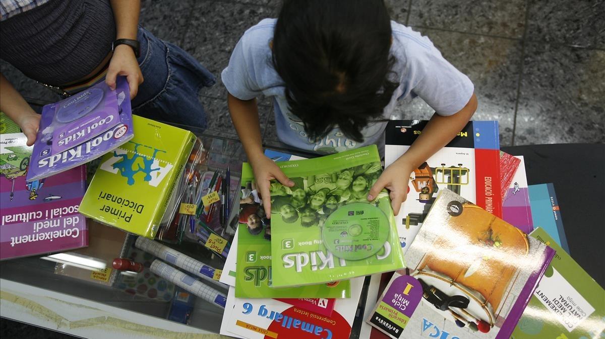 Dos niñas miran los libros de texto de su curso en la estantería de una librería.