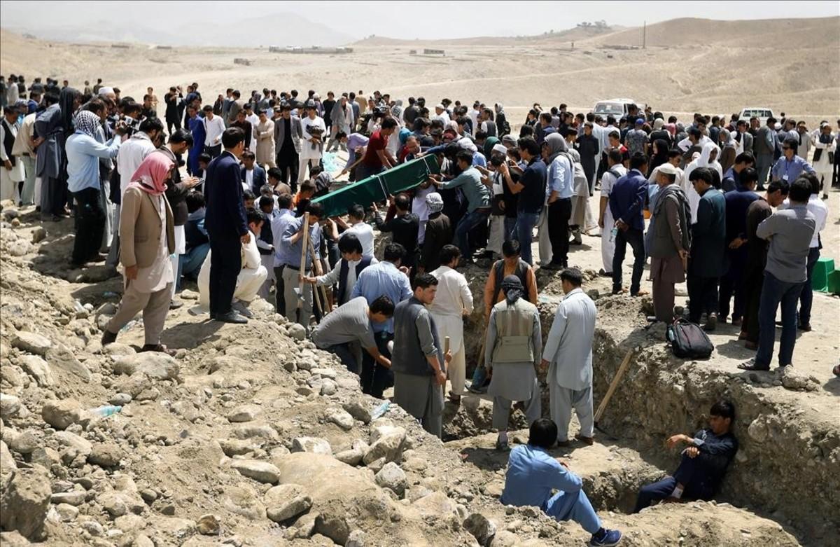 Una multitud asiste al funeral conjunto en Kabul, Afganistán, tras el ataque perpetrado contra un centro educativo en el que perdieron la vida decenas de estudiantes.