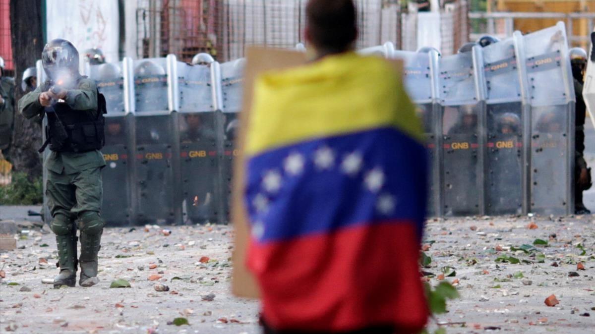 Un hombre con una bandera venezolana se enfrenta a las fuerzas de seguridad durante la Huelga General del 26 de julio.