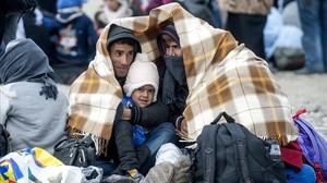 Inmigrantes se protegen del frío en un campo de refugiados tras cruzar la frontera entre Grecia y Macedonia.
