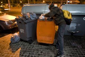 Un jove busca menjar en un contenidor d'escombraries orgàniques, a Barcelona.