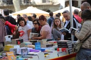 Unos lectores repasan librosen los puestos de venta que inundan Barcelona en una Diada de Sant Jordi.