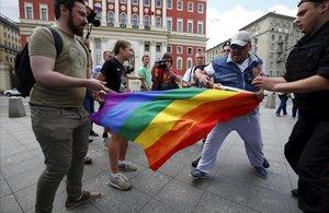 Manifestantes homófobos tratan de romper una bandera gay de un grupo de homosexuales en Moscú.