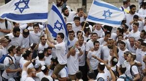 Manifestantes israelís celebran la aprobación de la ley en el Parlamento.