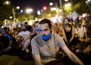 Manifestants davant el Congrés, ahir a la nit, amb un mocador a la boca per protestar contra la 'llei mordassa'.