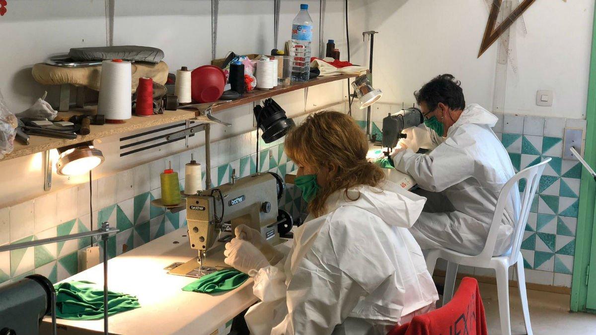 Unos voluntarios cosen mascarillas en la asociación de vecinos de Sentmenat.