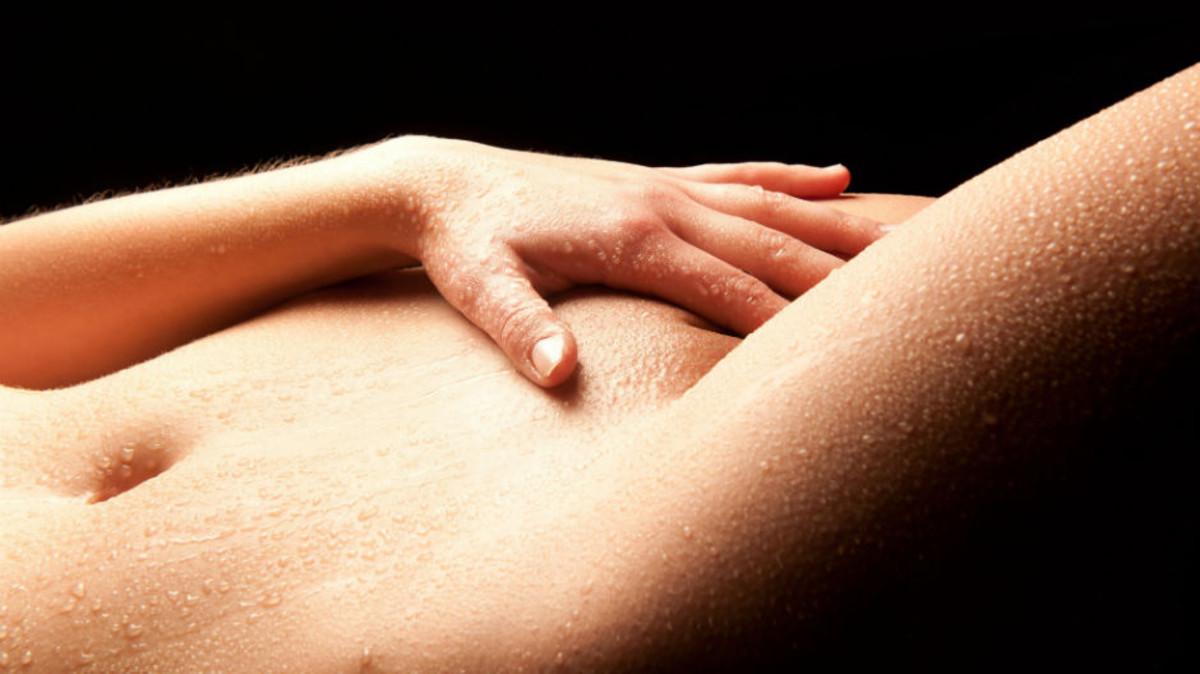 Una mujer toca sus genitales.