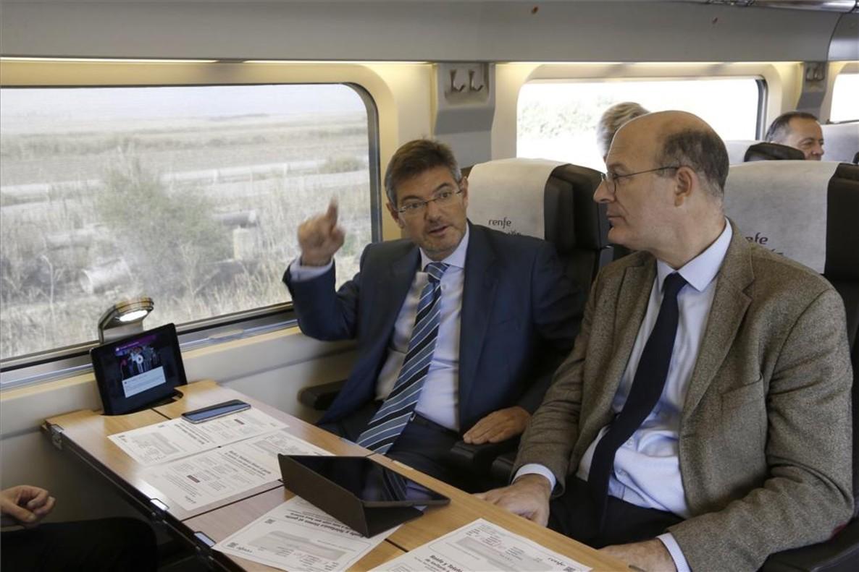 El ministro de Fomento en funciones, Rafael Catalá (izquierda), conversa con el presidente de Renfe, Pablo Vázquez, en el AVE donde han presentado el servicio de wifi.